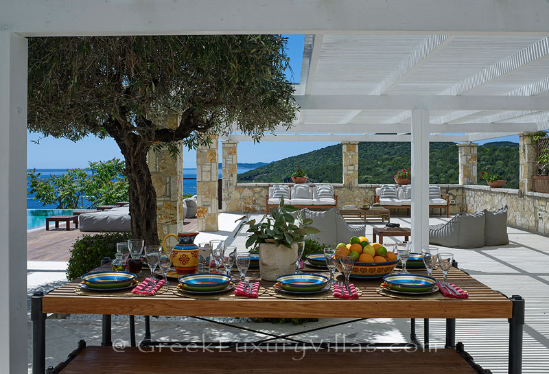 Outdoor dining area at a luxury villa with a heated pool in Sivota